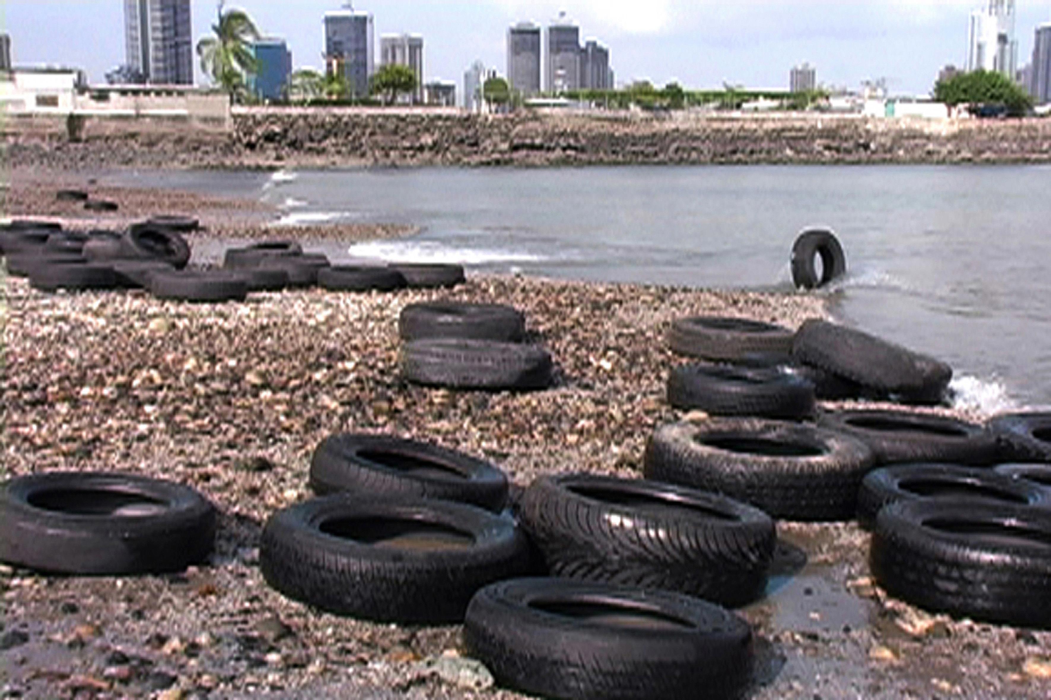 Donna Conlon. Marea baja (2004). Vídeo, 03'34'' en bucle. (Fotograma-vídeo con neumáticos en la orilla de la playa ante el skyline de Ciudad de Panamá).