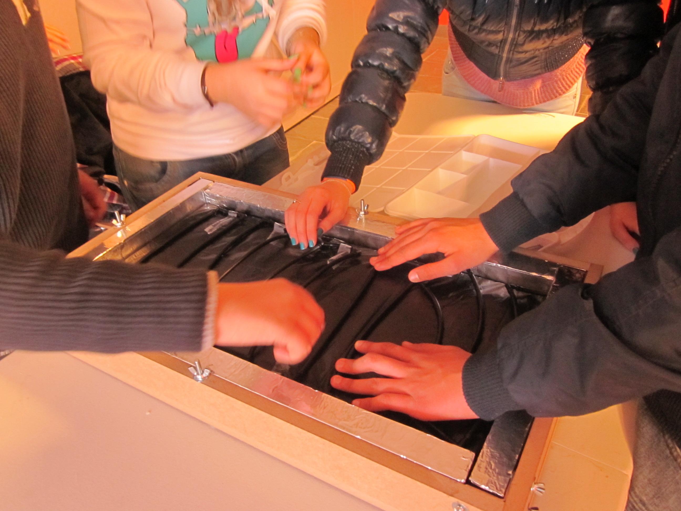 Jóvenes montando su propio panel solar térmico.