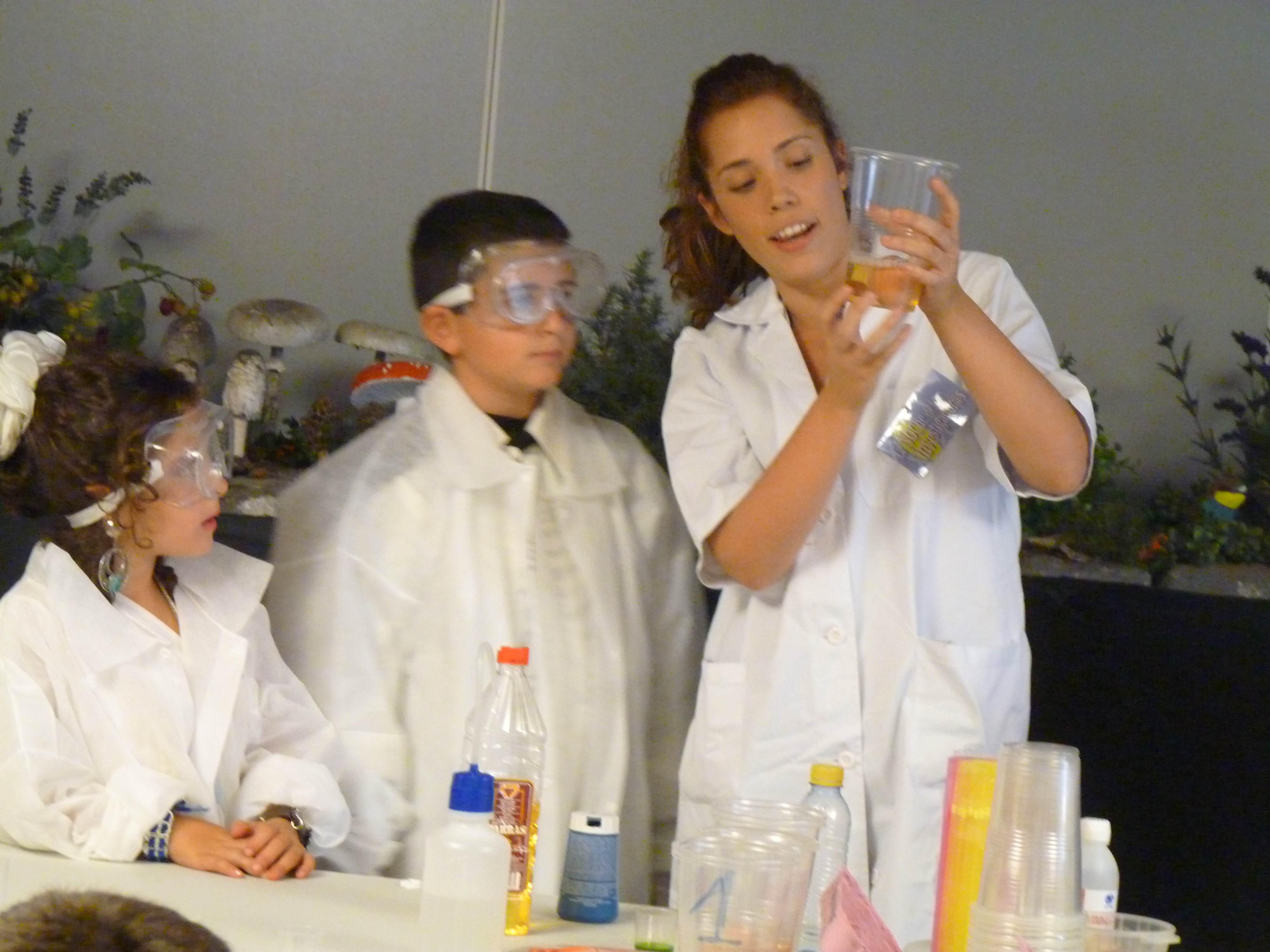 Una de las investigadoras muestra el resultado de un experimento a dos participantes